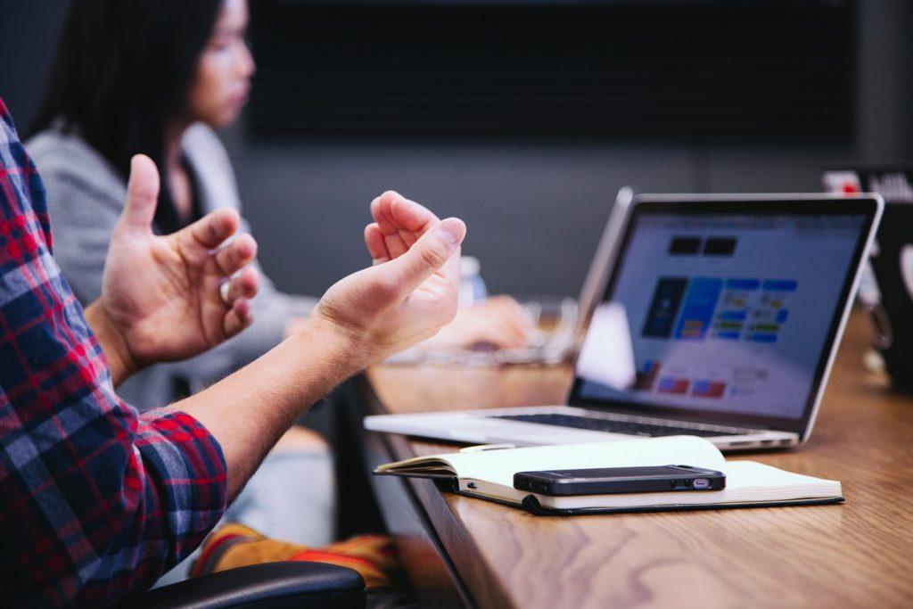 departamento de soporte IT interno trabajando en las decisiones de inversión en tecnología. Se ve un hombre hablando y una mujer de fondo. Hay una laptop abierta y un cuaderno sobre la mesa.