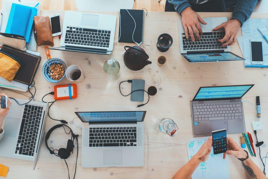 Departamento de Soporte IT externo. Vista de arriba, un equipo de trabajo de IT discute sobre una mesa llena de Macbooks y dispositivos tecnológicos.